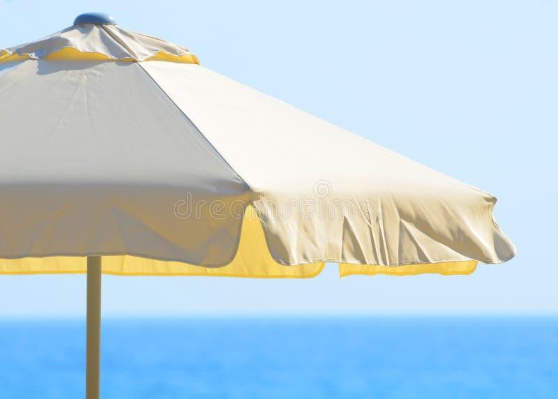 反对海和天空的沙滩伞 库存照片