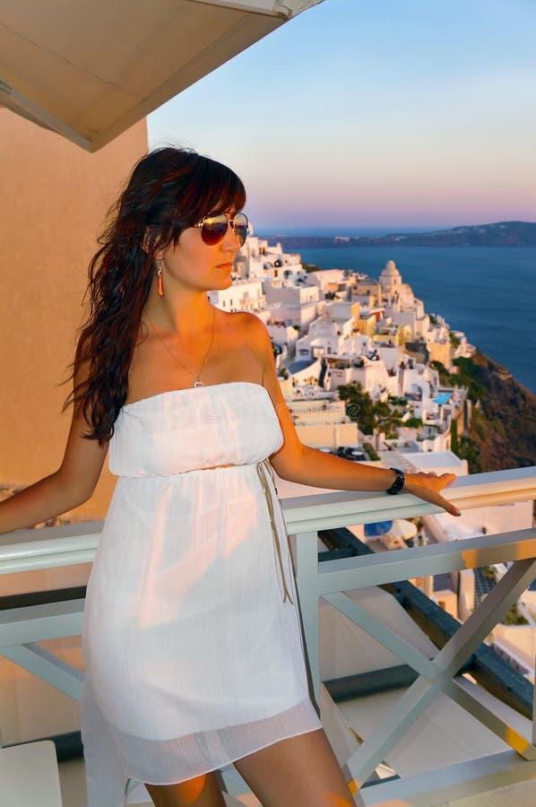 反对海岛圣托里尼衰落的美丽的女孩 图库摄影