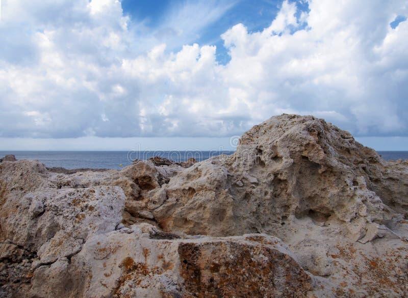 反对深蓝色海的坚固性岩石有与白色云彩的明亮的天空的在menorca西班牙旅行或假期背景 库存图片