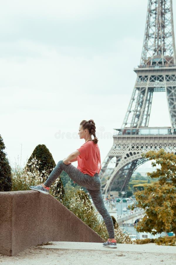 反对清晰视界的妇女慢跑者埃菲尔铁塔舒展 库存图片