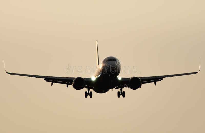 反对清楚的天空的喷气机着陆在黄昏 免版税图库摄影