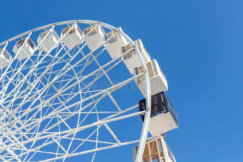反对清楚的天空蔚蓝的特写镜头大白色现代弗累斯大转轮在背景在基辅市中心 在其他中的一艘黑长平底船 库存图片