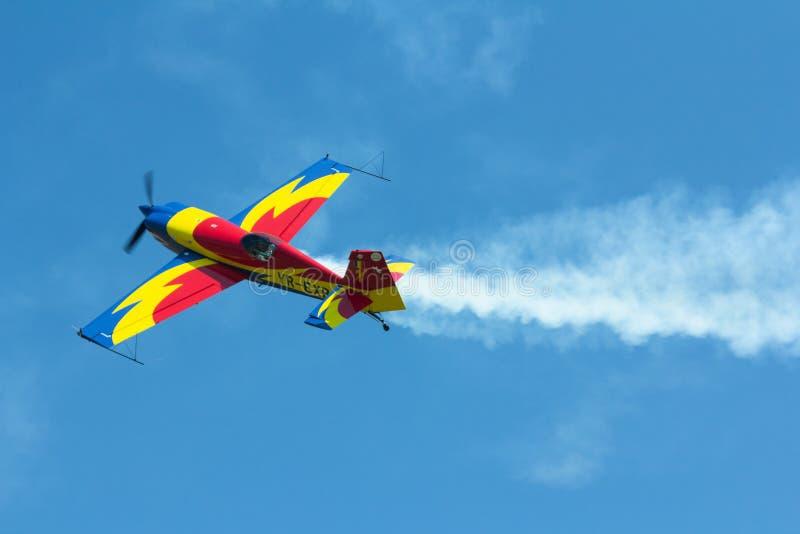 反对清楚的天空蔚蓝的特技平面飞行 免版税库存照片