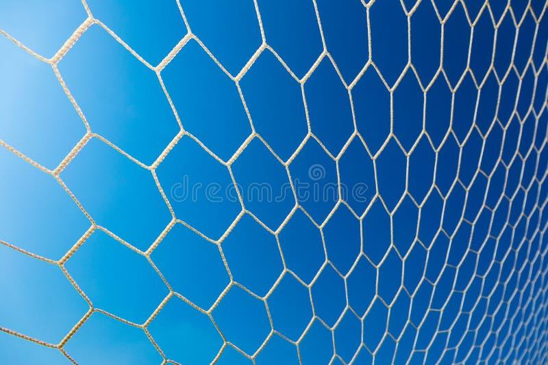 反对清楚的蓝天的白色足球或橄榄球目标网 图库摄影