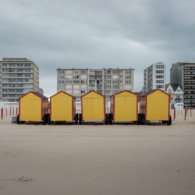 反对灰色天空和背景的五个五颜六色的海滩小屋 库存照片