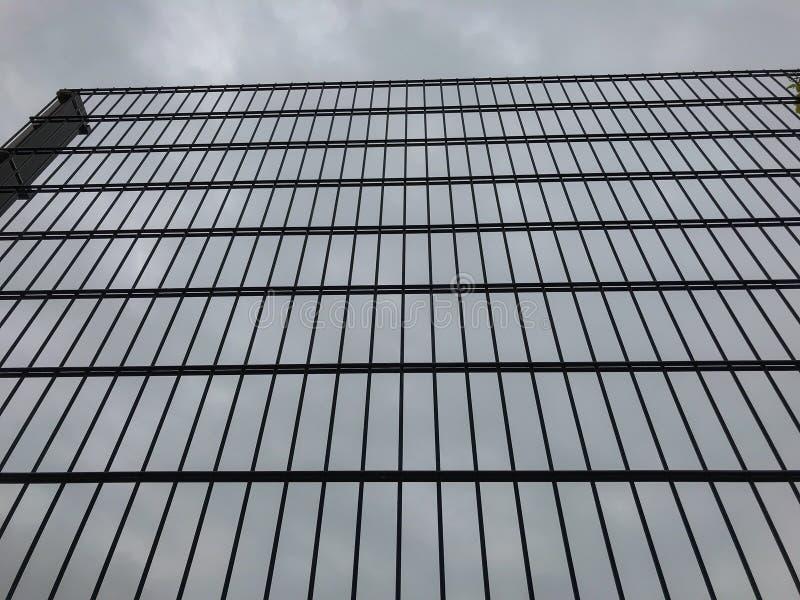 反对灰色天空的高金属篱芭 边界或监狱概念 库存照片