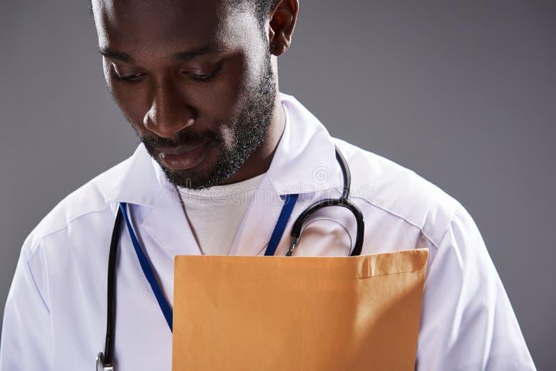 反对灰色背景的严肃的美国黑人的男性医生身分 免版税库存照片