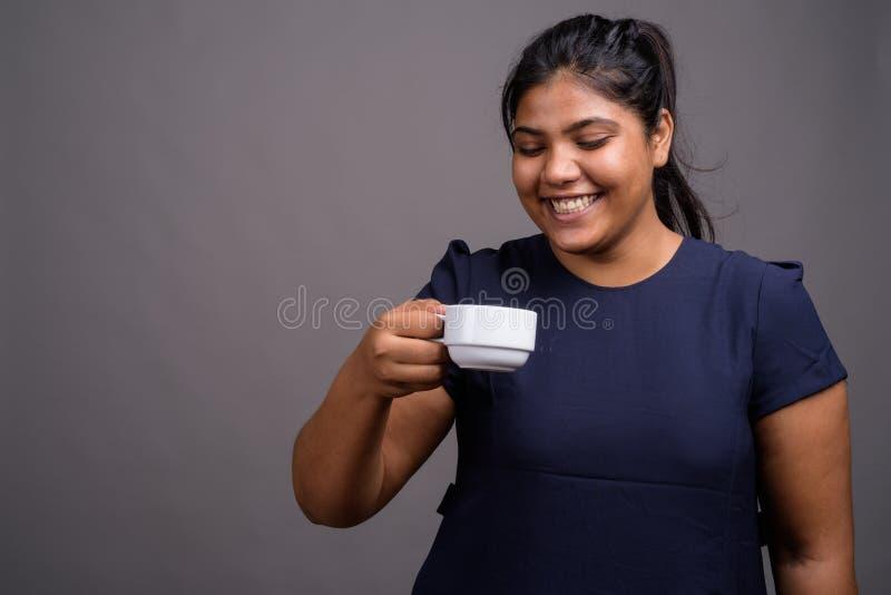反对灰色背景的年轻超重美丽的印度妇女 免版税库存照片