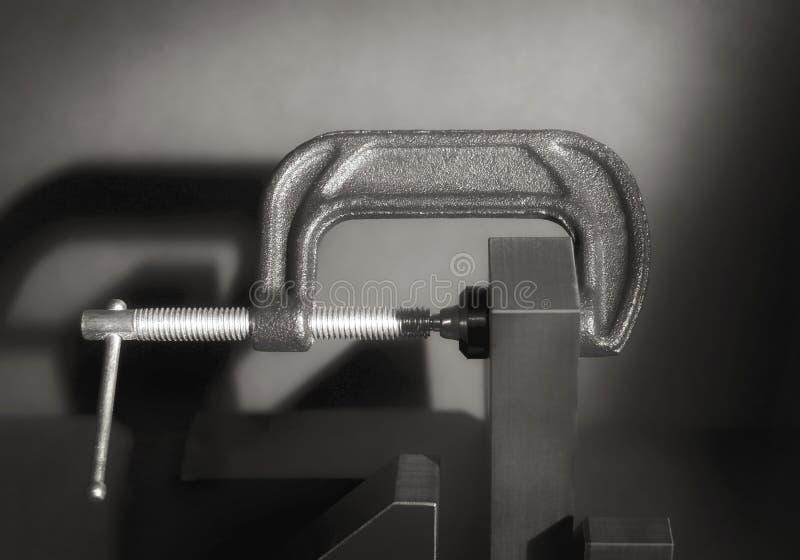 反对灰色背景的灰色金属C钳位 库存照片