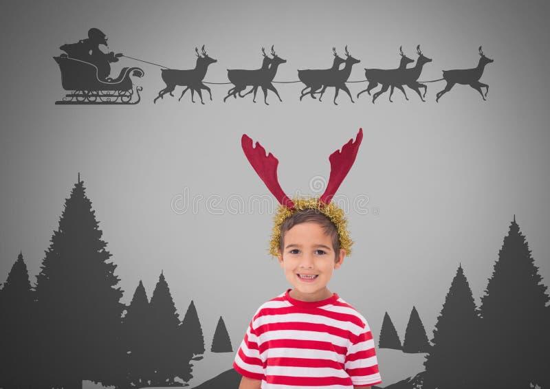 反对灰色背景的男孩与在头和圣诞老人飞行的驯鹿鹿角在雪橇 库存例证