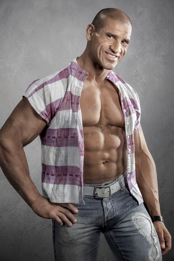反对灰色背景的肌肉微笑的年轻人 库存照片