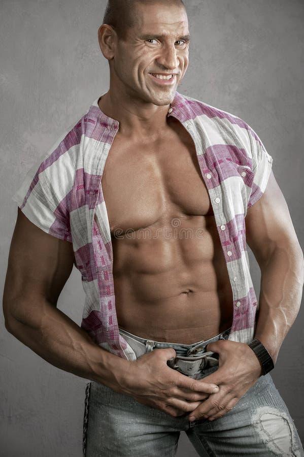 反对灰色背景的肌肉微笑的年轻人 库存图片