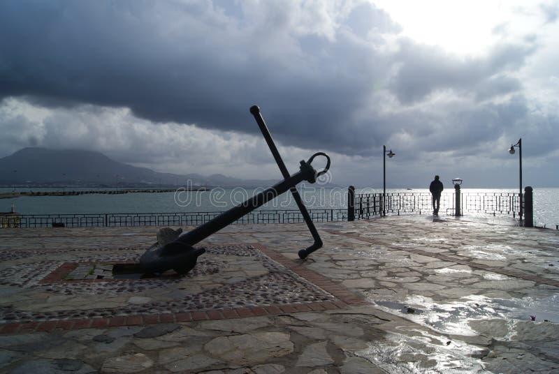 反对灰色蓝色云彩的老船的船锚 免版税库存照片