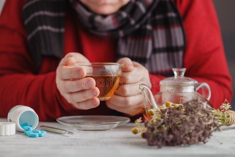 反对热病的热的茶 男性看在thermom的温度 免版税库存照片