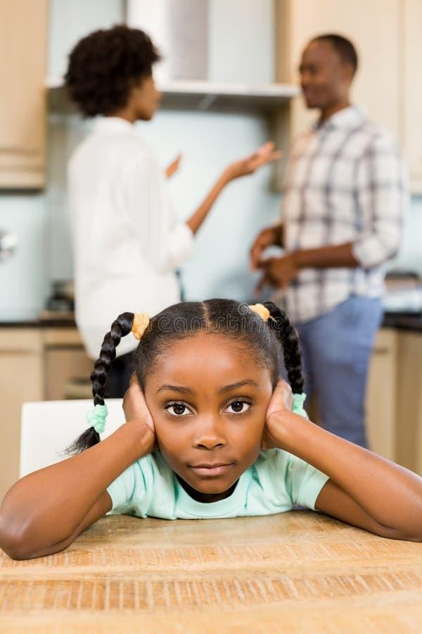 反对父母争论的哀伤的女孩 库存图片