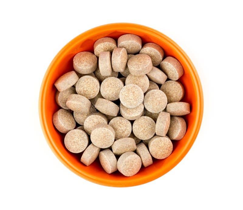反对白色的橙色草本多种维生素药片片剂 图库摄影