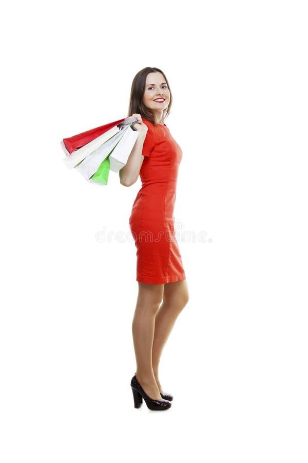 反对白色背景的愉快的少妇运载的购物袋 库存图片