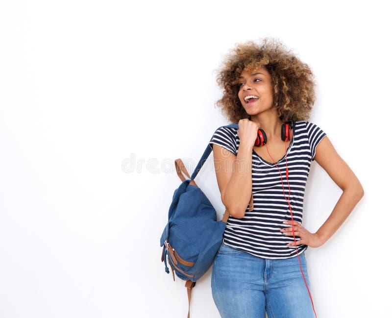 反对白色背景的愉快的年轻黑人女学生 免版税库存图片