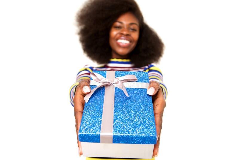 反对白色背景的愉快的年轻黑人妇女藏品礼物盒 图库摄影