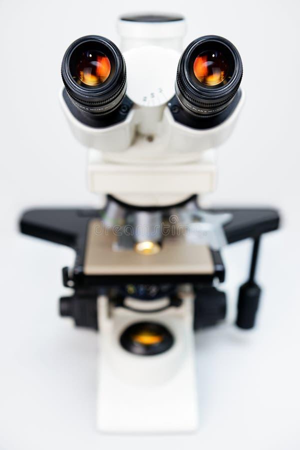 反对白色背景的显微镜 免版税库存照片