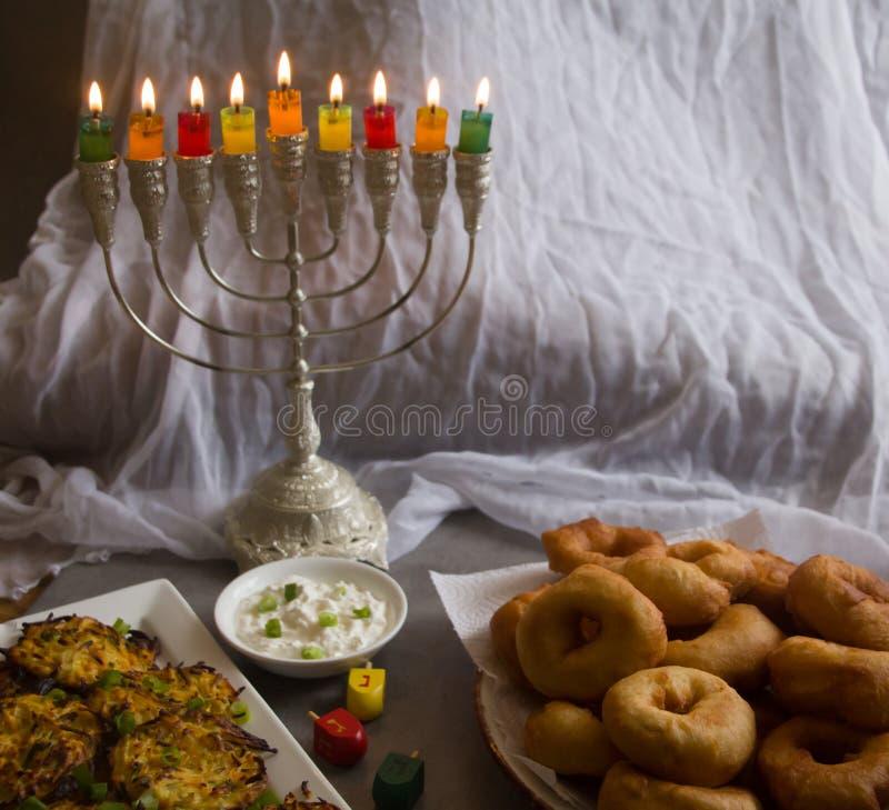 反对白色背景的犹太假日光明节标志;传统抽陀螺,menorah传统大烛台,'Sfinj'Donu 免版税库存照片