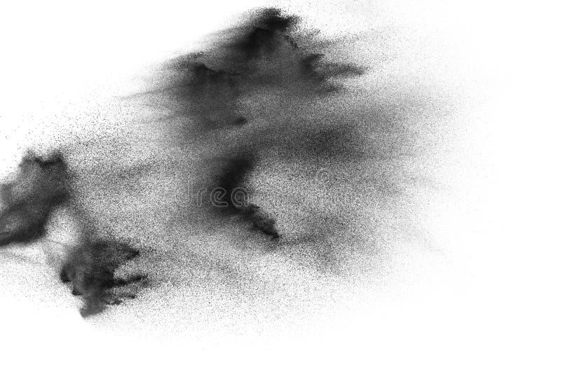反对白色背景的黑沙子爆炸 在白色背景喷溅的沙子微粒 库存图片