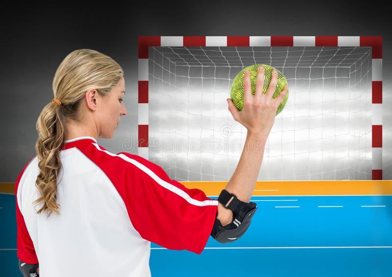 反对目标岗位的女运动员投掷的手球在背景中 免版税库存照片