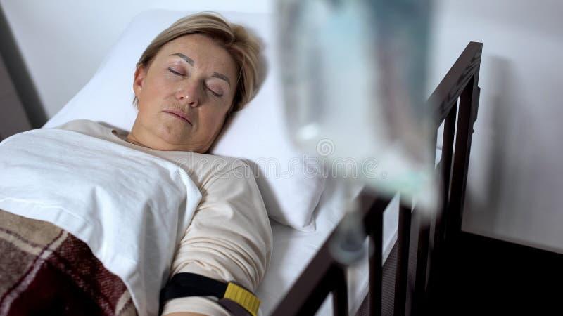 反对睡觉在医院病房里的微弱的资深患者的吸管身分,疗法 免版税库存照片