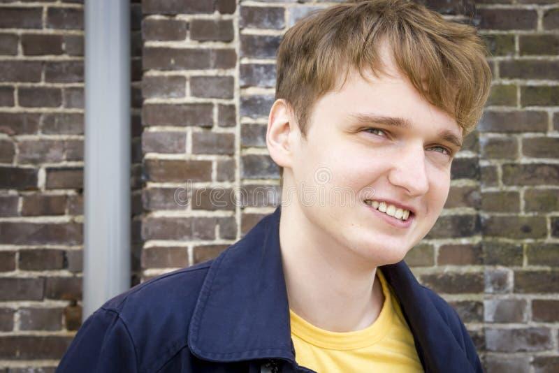 反对砖墙微笑的英俊的年轻人 免版税库存图片