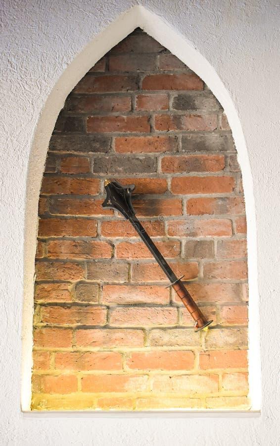 反对砖墙背景的中世纪尖铁钉头锤 免版税图库摄影