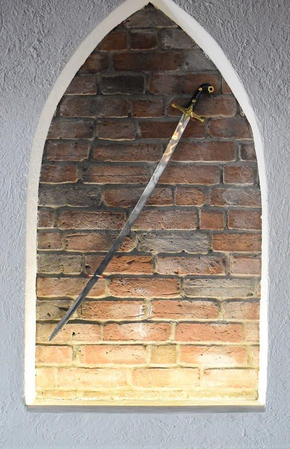 反对砖墙背景的中世纪钢剑 作为装饰使用的古老光亮的剑 库存照片
