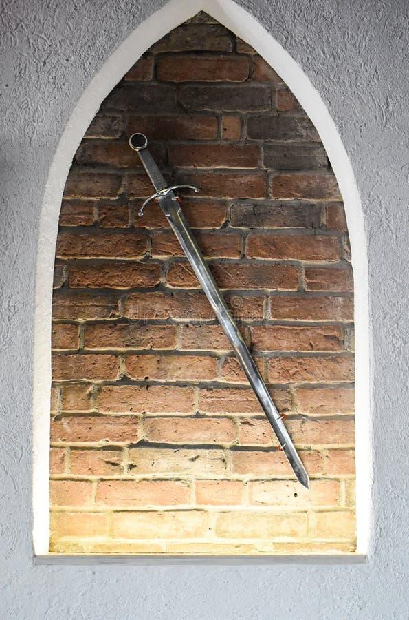 反对砖墙背景的中世纪钢剑 作为装饰使用的古老光亮的剑 免版税图库摄影