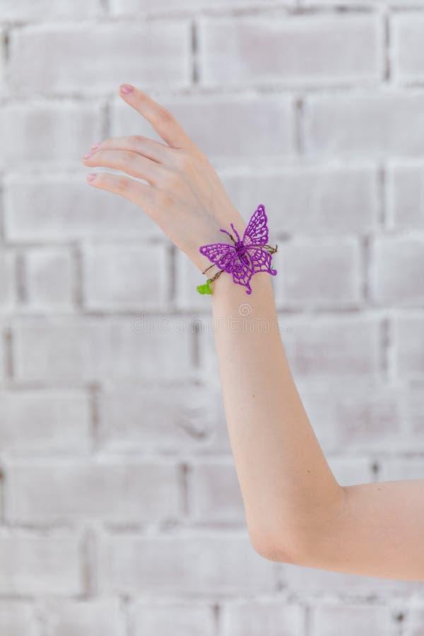 反对砖墙背景的女孩的手  免版税图库摄影