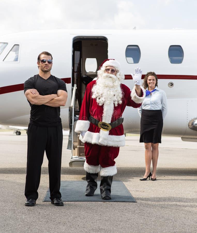 反对私人喷气式飞机的圣诞老人挥动的手 库存照片