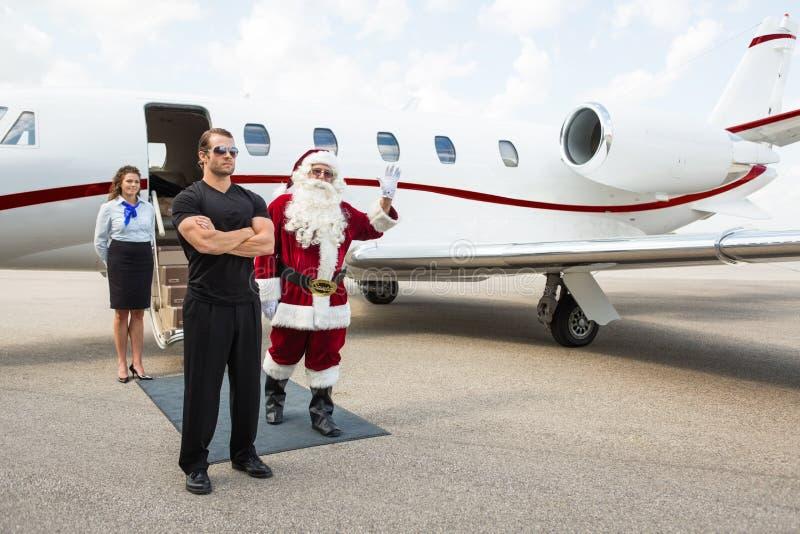 反对私人喷气式飞机的圣诞老人挥动的手 免版税库存照片