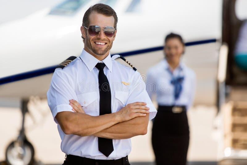 反对空中小姐和私人喷气式飞机的确信的飞行员 免版税库存图片