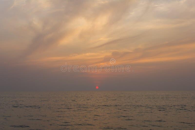 反对紫色日落天空的海洋与明亮的红色太阳 免版税库存照片