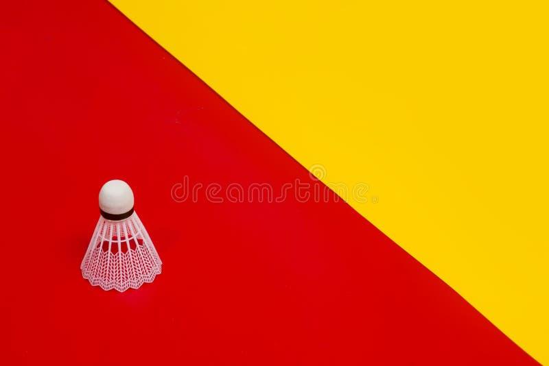 反对红色和黄色背景的羽毛球shuttlecock 库存图片