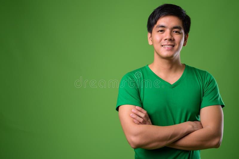 反对绿色背景的年轻英俊的菲律宾人 免版税库存照片