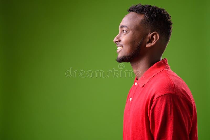反对绿色背景的年轻英俊的非洲人 免版税库存图片