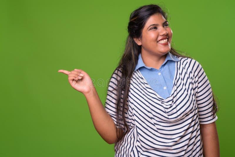 反对绿色背景的年轻超重美丽的印地安女实业家 库存照片