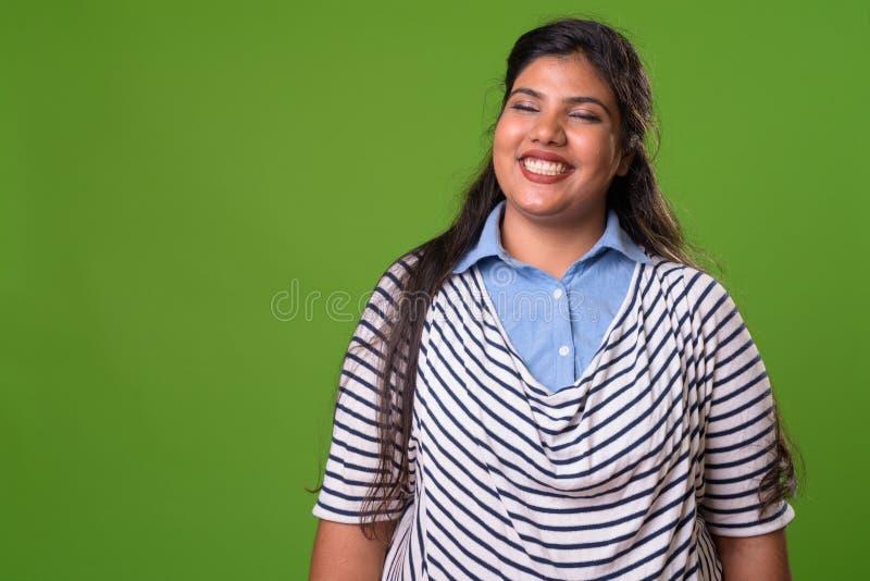 反对绿色背景的年轻超重美丽的印地安女实业家 库存图片