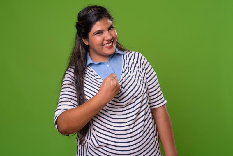 反对绿色背景的年轻超重美丽的印地安女实业家 免版税图库摄影