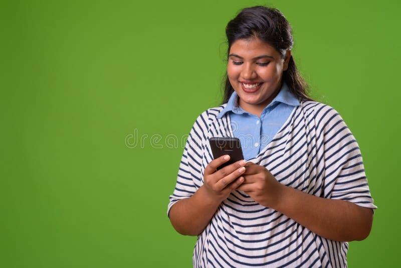 反对绿色背景的年轻超重美丽的印地安女实业家 免版税库存图片