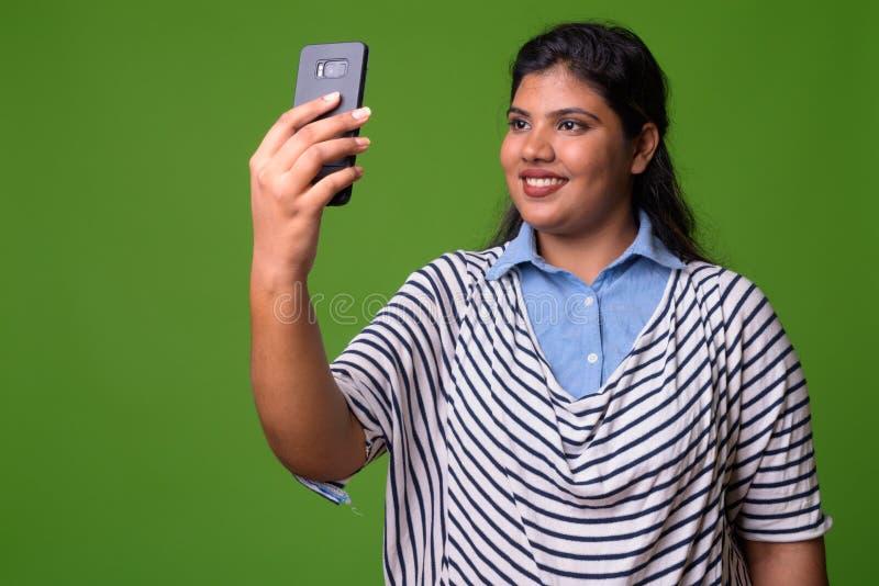 反对绿色背景的年轻超重美丽的印地安女实业家 免版税库存照片