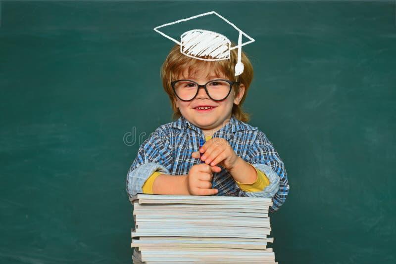 反对绿色黑板的学校孩子 小学和教育 有天才的孩子 第一时代 孩子准备好 免版税库存图片