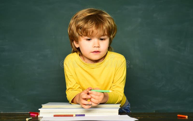 反对绿色黑板的学校孩子 小学和教育 ?? ?? o 免版税库存照片