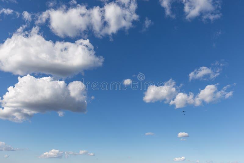 反对美丽的深,蓝天的一次滑翔伞飞行,与大白色云彩 图库摄影