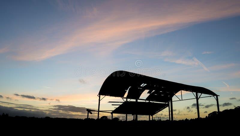 反对美好的充满活力的日落landsc的遗弃谷仓剪影 库存照片