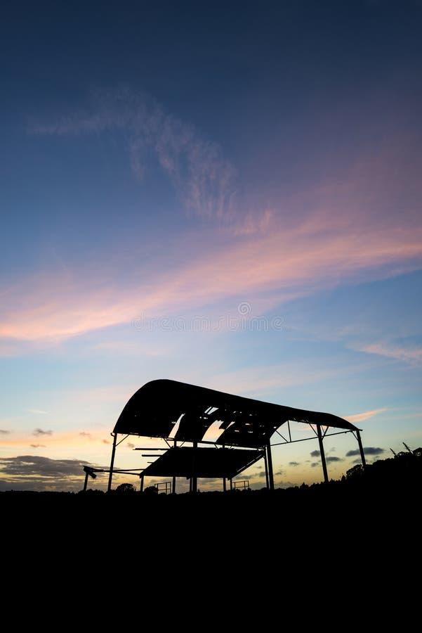 反对美好的充满活力的日落landsc的遗弃谷仓剪影 库存图片